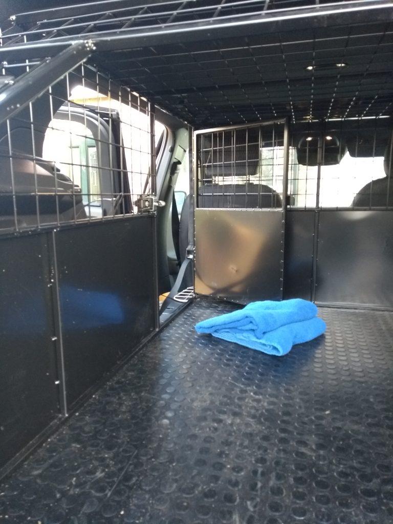 Dog transport cage escape hatch